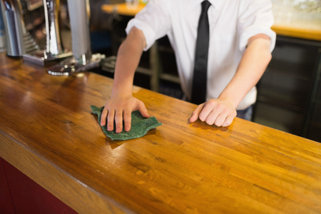 Mid section of bartender cleaning bar counter