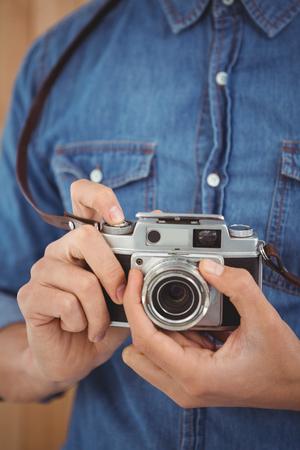 adjusting: Cropped image of man adjusting camera lens