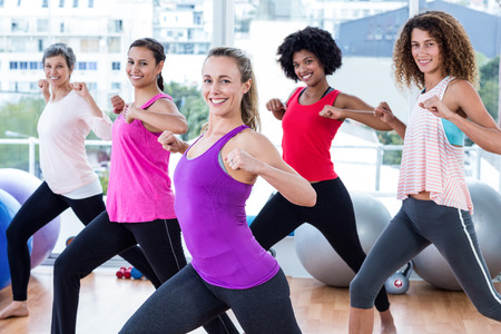 clasped hands: Portrait of women exercising with clasped hands and stretching in fitness studio Stock Photo