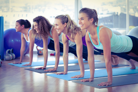 Women smiling while doing plank pose on exercise mat in fitness center Foto de archivo
