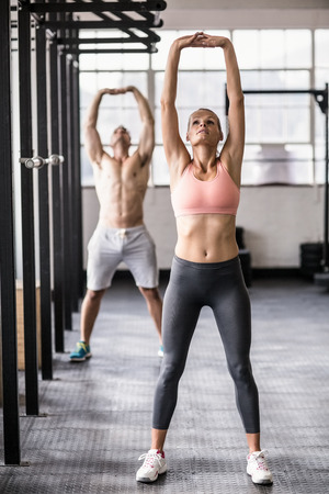 gym: Two fit people doing fitness in crossfit gym