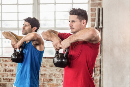 kettle bell: Muscular men lifting a kettle bell in crossfit gym