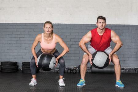 crossfit: Muscular couple doing ball exercise in crossfit gym Stock Photo