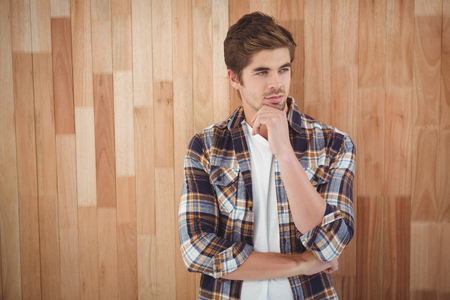 chin: Confident businessman standing with hand on chin against wooden wall Stock Photo