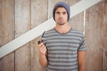 hombre con sombrero: Retrato del inconformista sosteniendo pipa de fumar mientras está de pie contra la pared de madera