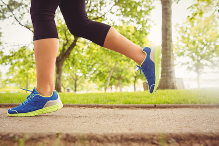 low section: Low section of woman wearing sport shoes jogging in park Stock Photo