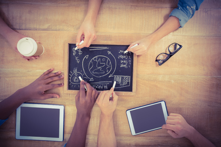 person writing: Overhead view of cropped hands writing business terms on slate with person touching digital tablet at table Stock Photo