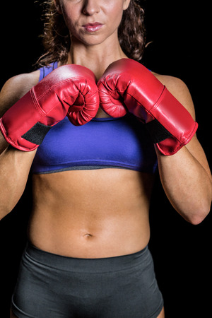 fighting stance: Midsection of female boxer with fighting stance against black background