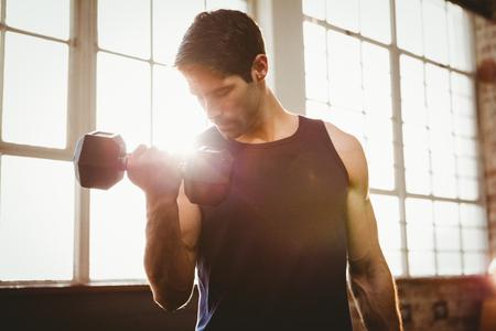 thin man: Hombre guapo mancuerna en el gimnasio levantando