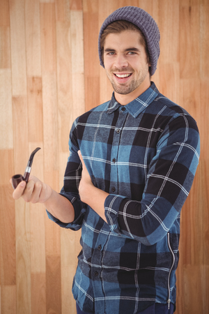 smoking pipe: Portrait of happy man holding smoking pipe while standing against wooden wall