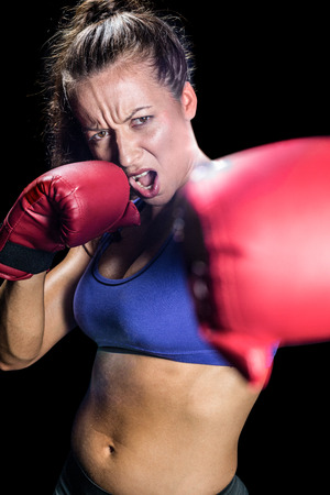 fighting stance: Portrait of aggressive female boxer with fighting stance against black background