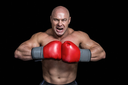 punched out: Angry bald boxer with punching gloves against black background