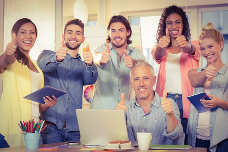 Portrait of confident business people with technologies showing thumbs up in creative office