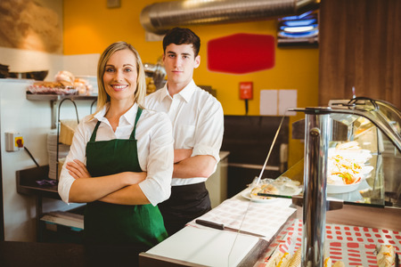 small business team: Portrait of confident coworkers by display cabinet in bakery Stock Photo