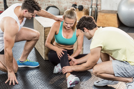 sports club: Muscular woman having an knee injury in crossfit gym Stock Photo