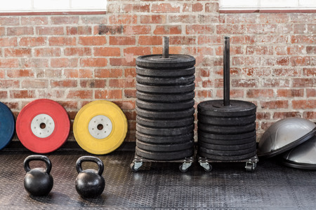 kettlebells in front of weights and bossu in crossfit gym