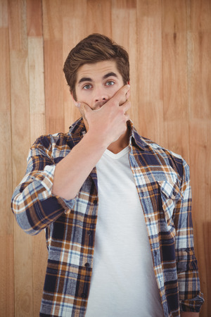 wall covering: Portrait of shocked hipster covering mouth against wooden wall