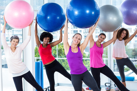 Portrait of smiling women holding exercise balls with arms raised in fitness studio Stock Photo