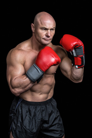 shaved head: Bald boxer with red gloves against black background