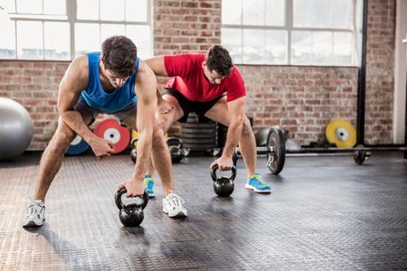 Los hombres que hacen ejercicio con pesas rusas en el gimnasio