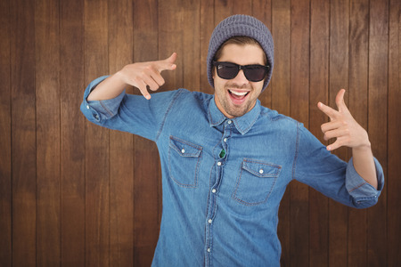 hand sign: Happy hipster showing rock and roll hand sign against wooden wall
