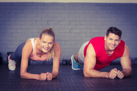 planking: Fit smiling couple planking together in gym in crossfit gym Stock Photo