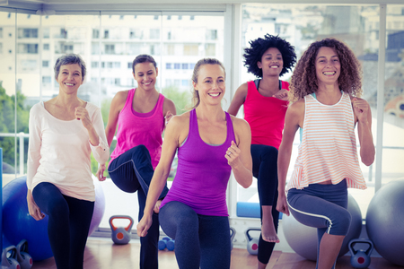 clasped: Smiling women exercising with clasped hands in fitness studio Stock Photo