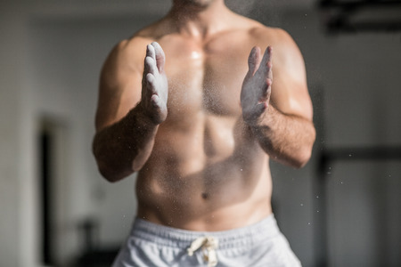 hands off: Muscular man shaking chalk off his hands in crossfit gym