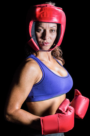 headgear: Portrait of pretty boxer with headgear and gloves against black background
