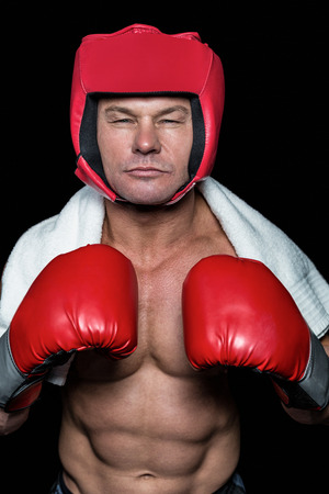 headgear: Confident boxer with gloves and headgear against black background