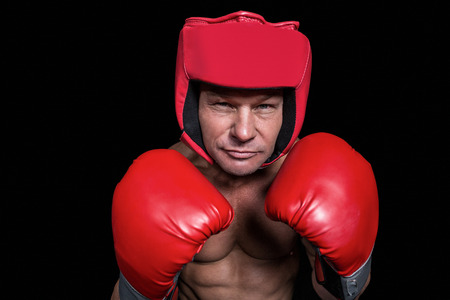 headgear: Portrait of boxer with gloves and headgear against black background