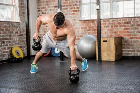 culturista: Hombre sin camisa kettlebell levantar en el gimnasio
