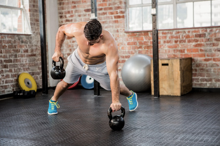 gym: Shirtless man lifting kettlebell at the gym Stock Photo