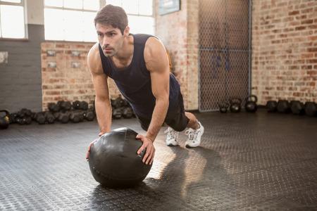 medicamento: Hombre que hace pectorales en bola de la medicina en el gimnasio Foto de archivo