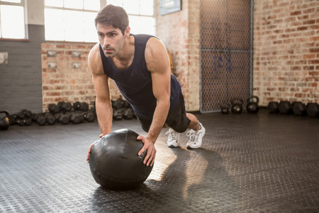 Man tut Push-ups auf Medizinball in der Turnhalle Standard-Bild