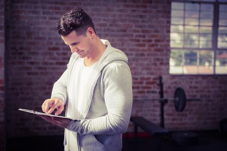 fitness hombres: Hombre muscular que sostiene el sujetapapeles en el gimnasio