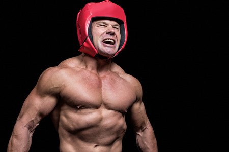 headgear: Angry boxer with red headgear against black background Stock Photo