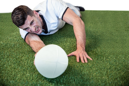 man lying down: Man lying down while holding ball over the grass Stock Photo
