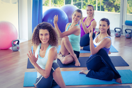 twisting: Portrait of happy women doing spine twisting pose on exercise mat