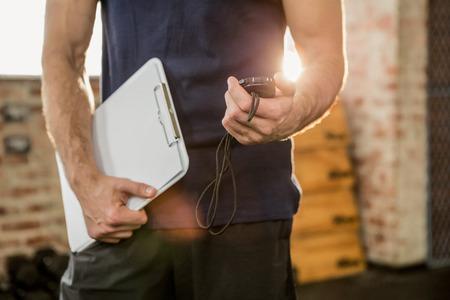 équipement: Médiane de l'entraîneur tenant presse-papiers et le chronomètre à la gym