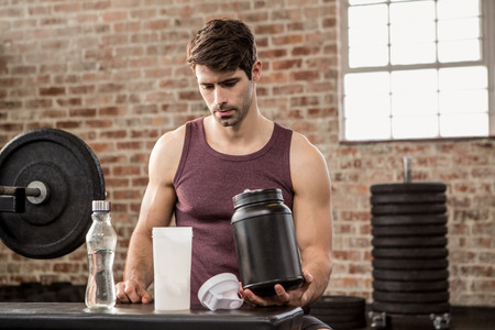 gym room: Man holding supplement tin at the gym Stock Photo