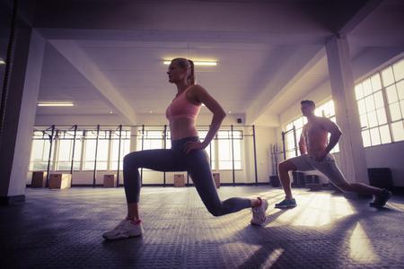 hombre flaco: Dos personas en forma haciendo fitness en el gimnasio de crossfit Foto de archivo