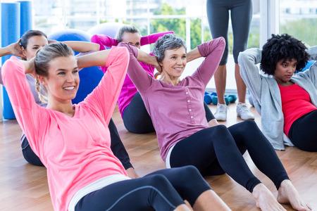 actividad fisica: Las mujeres atractivas que hace el sit ups en el piso de madera en gimnasio
