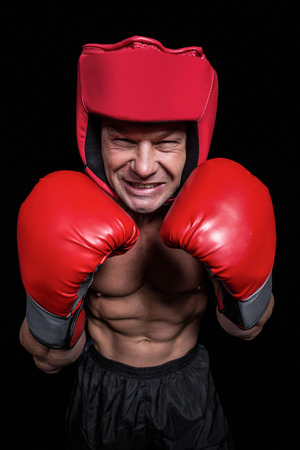 headgear: Angry boxer with gloves and headgear against black background
