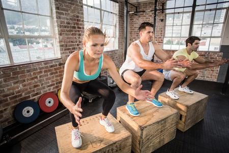 saltando: Las personas en forma haciendo caja de salto en gimnasia crossfit