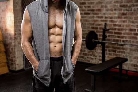 Midsection of man wearing hood at the gym
