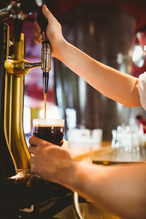 Cropped hand of bartender holding glass below beer dispenser tap at bar counter