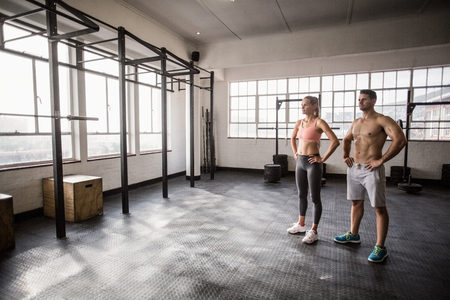 lean out: Crossfit couple posing with hands on hips In crossfit gym