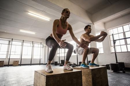 fitnes: Gespierde paar doen springen kraakpanden in CrossFit sportschool Stockfoto