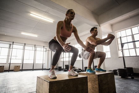 fitness club: Muscular couple doing jumping squats in crossfit gym